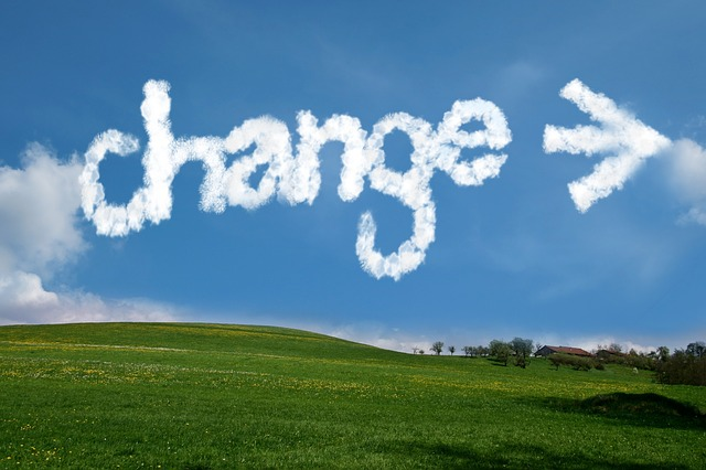 Blue sky with cloudy words saying change. Grass field in background.